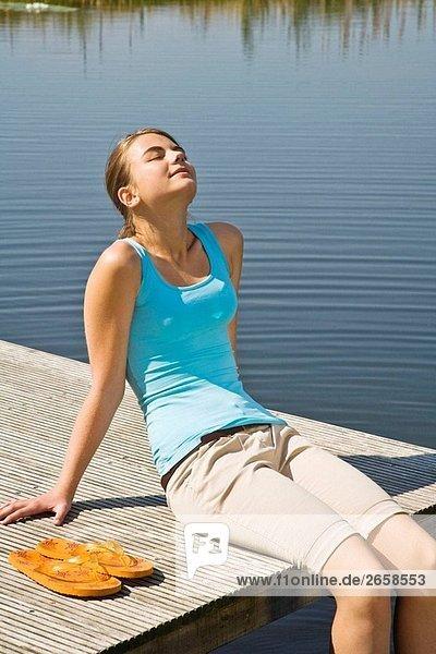 Junges Mädchen Sonnenbaden an einem See