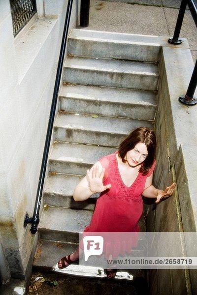 Junge Frau zu Fuß nach unten eine Reihe von konkreten Treppen.