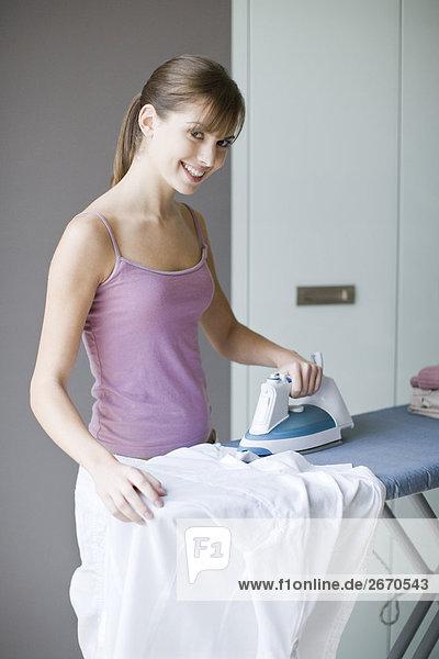 junge Frau junge Frauen Bügeleisen Kleidung