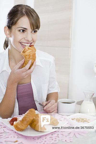Frau isst croissant