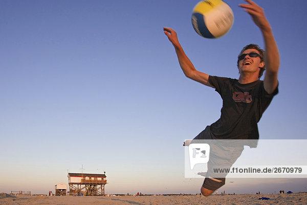 Junger Mann beim Beachvolleyball am Strand von Sankt Peter Ording