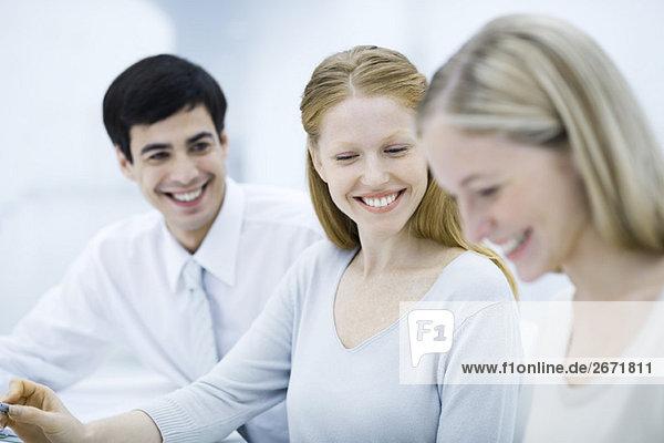 Junge Profis lächeln  Fokus auf Frau in der Mitte sitzend