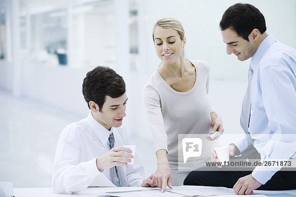Three professionals taking a coffee break  woman pointing at newspaper