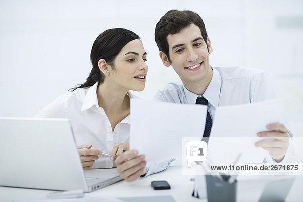Profis arbeiten zusammen am Schreibtisch  Mann mit Unterlagen