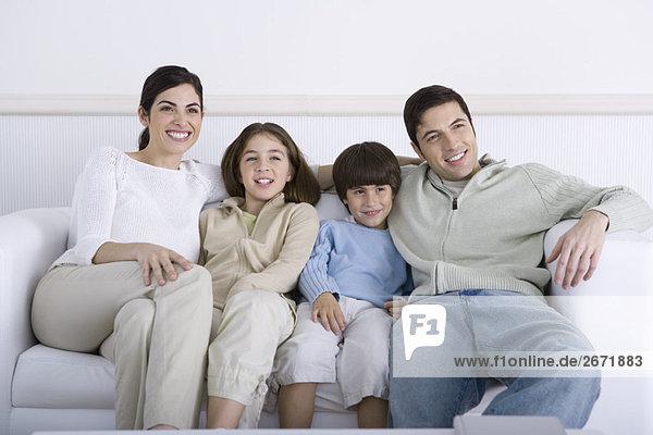 Familie sitzt zusammen auf dem Sofa und schaut weg.