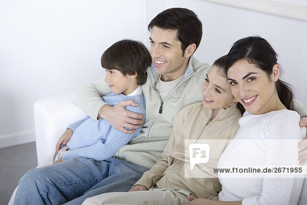 Family sitting together on sofa  looking away  woman smiling at camera