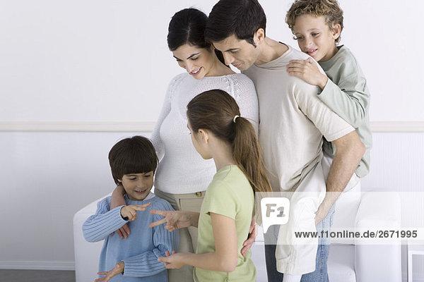 Familie steht zusammen und sieht Sohn und Tochter spielen ''Steinpapierschere'''.