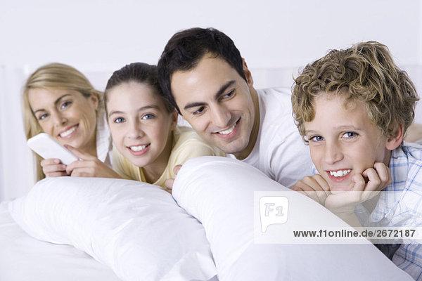 Familie entspannt sich zusammen im Bett  lächelt in die Kamera  Vater schaut auf Sohn