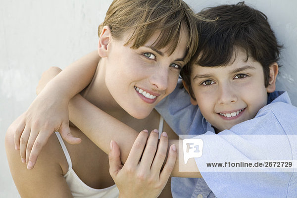 Mother and son embracing  both smiling at camera