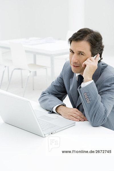 Geschäftsmann im Gespräch am Handy  am Laptop sitzend