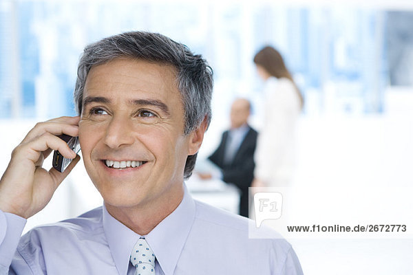 Businessman using cell phone in office  looking up  smiling