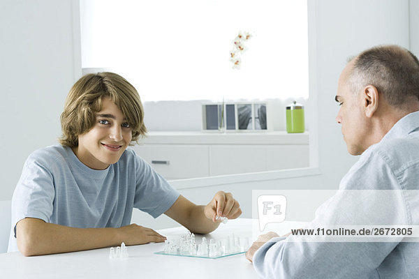 Jugendlicher Junge  der mit Vater Schach spielt  lächelt vor der Kamera.
