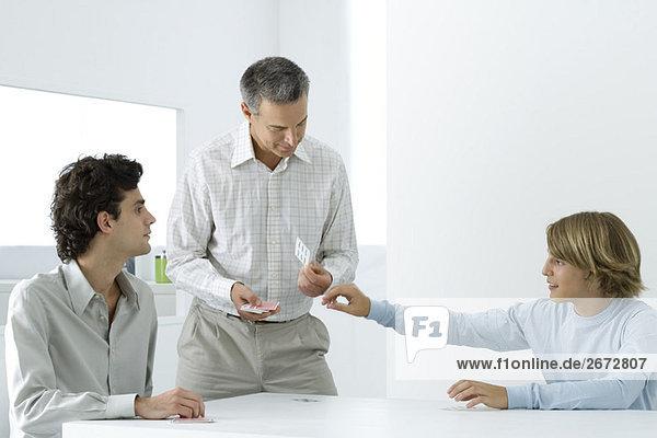 Reifer Vater und zwei Söhne beim Kartenspielen