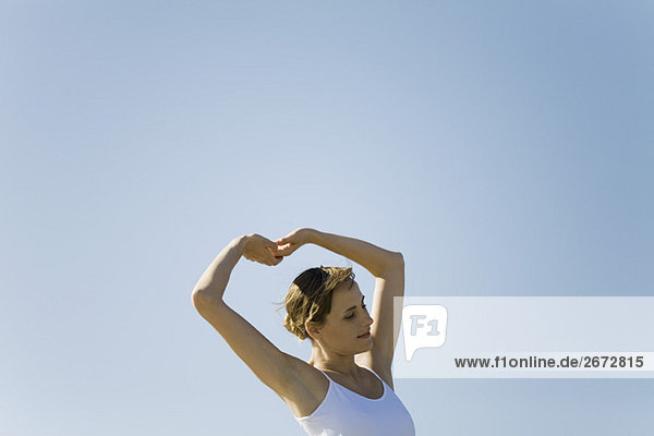 Woman standing outdoors stretching arms above head  eyes closed