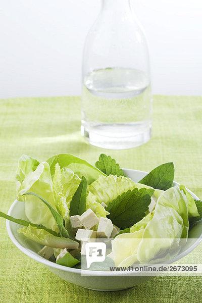 Salat von mixed grünen und Tofu Cubes,  Karaffe Wasser im Hintergrund