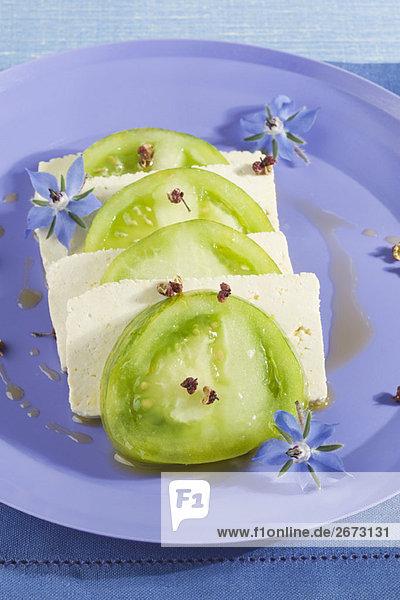 Abwechselnde Scheiben Grüne Tomaten und Tofu angeordnet auf einer blauen Platte