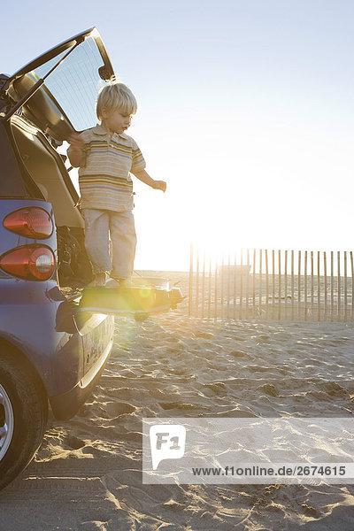 Junge stehend auf der Rückseite des Cost am Strand