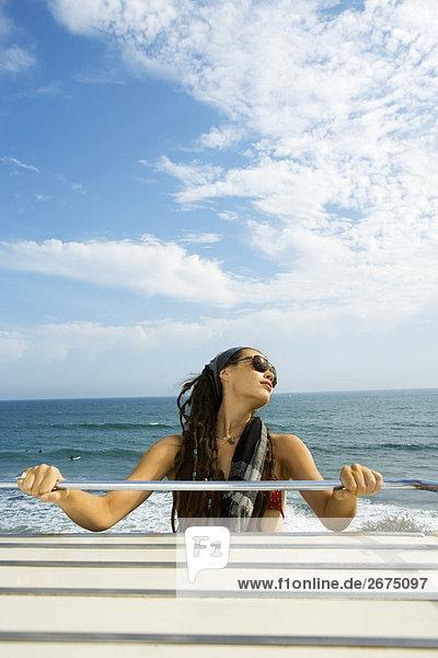 Frau mit Sonnenbrille auf Oldtimer am Strand