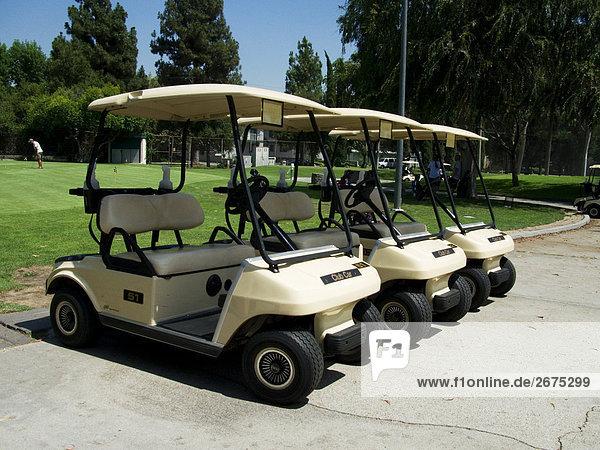 Drei geparkte Golf-carts