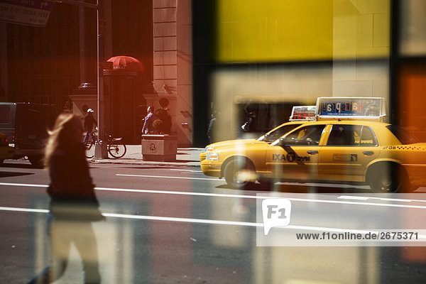 Reflective view of busy street in New York
