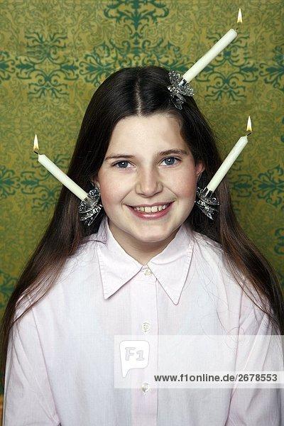 Porträt des Mädchens mit brennende Kerzen auf dem Kopf