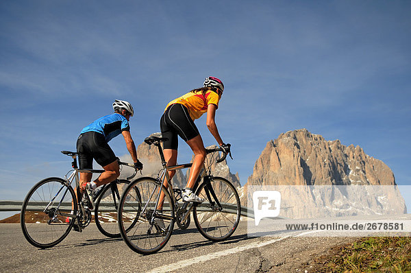 Rear view of two mountain bikers cycling together  Dolomites  Italy