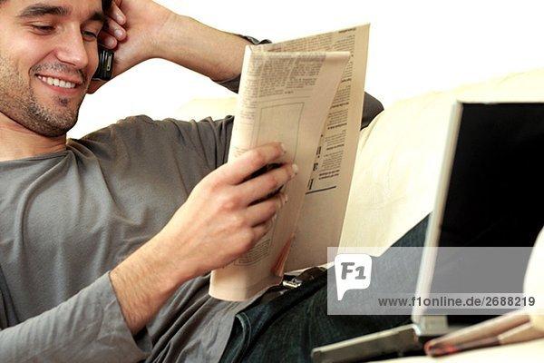 Junger Mann eine Zeitung lesen und sprechen auf einem Mobiltelefon
