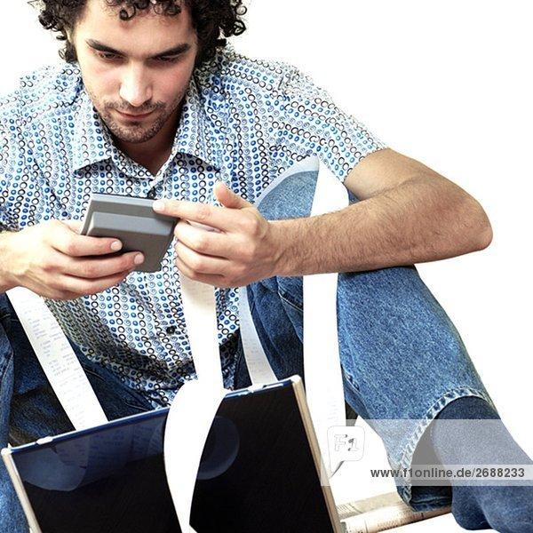 Junger Mann sitzend an einen Laptop halten einen Taschenrechner