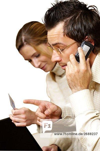Geschäftsfrau hält eine Kreditkarte mit einem Geschäftsmann auf einem Mobiltelefon neben ihr sprechen
