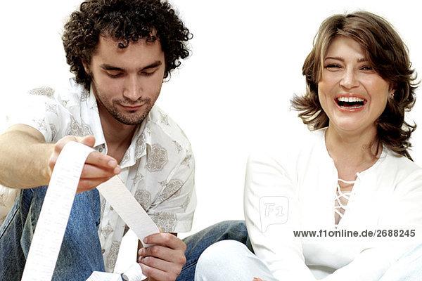 Portrait einer jungen Frau lacht mit Blick auf eine Quittung junger Mann