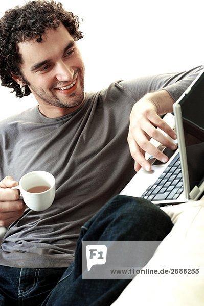 Junger Mann mit eine Tasse Tee mit einem laptop