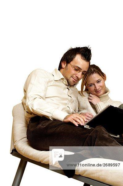 Kaufmann und eine geschäftsfrau liegender auf eine Chaise lounge mit einem Laptop vor