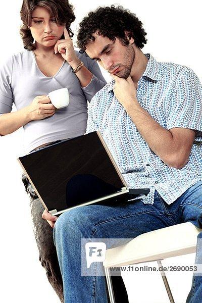 junges Paar denken während der Arbeit auf einem laptop