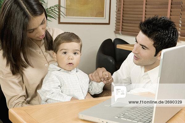 Portrait eines jungen Baby sitzen vor einem Laptop mit seinen Eltern