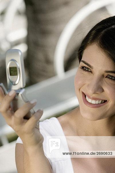 Nahaufnahme of a junge Frau hält ein Mobiltelefon