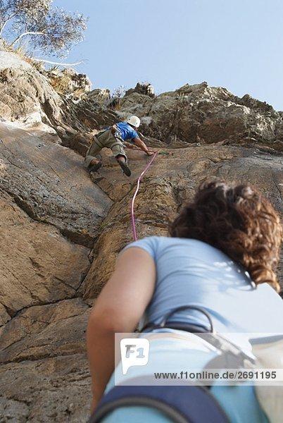 Untersicht of a female Rock Climber Blick auf ein männlich Steinbergsteiger Skalierung eine Felswand