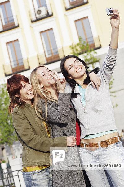 Junge Frau ein Foto von sich selbst mit zwei Freunden