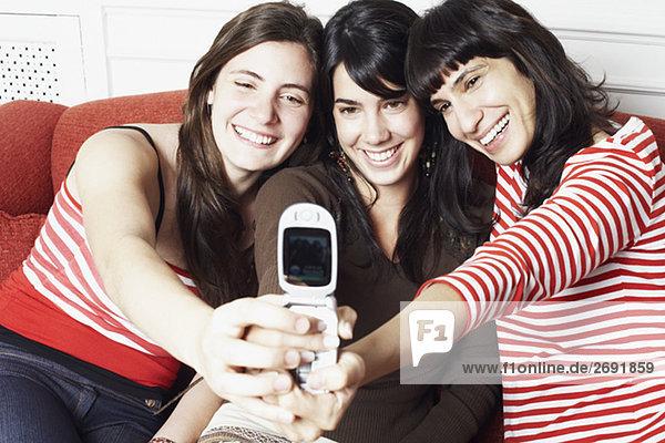 Zwei junge Frauen und eine Mitte erwachsen frau ein Foto von sich selbst mit einem Mobiltelefon