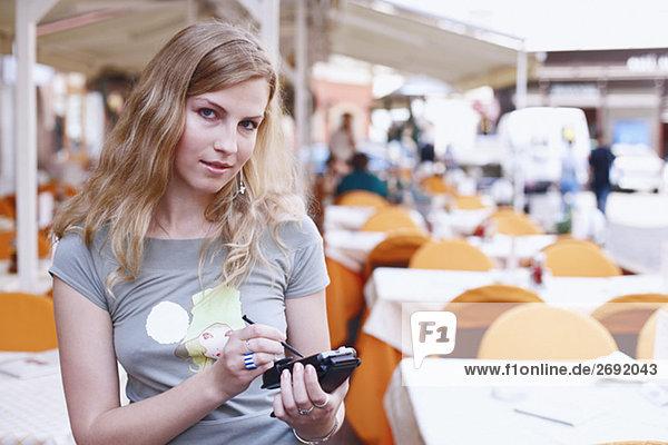 Portrait of a junge Frau hält ein persönlicher Datenassistent