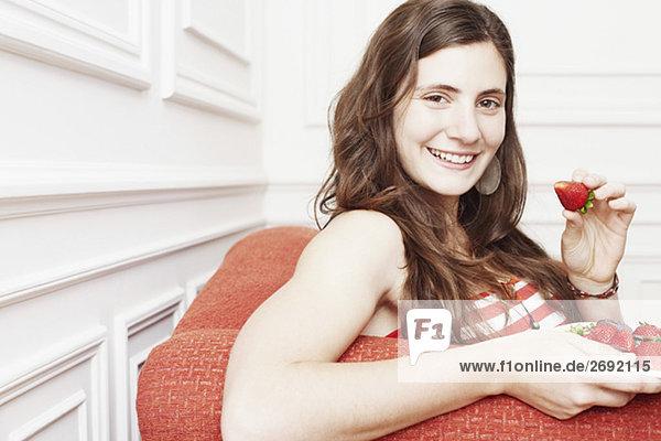 Portrait einer jungen Frau hält einen Teller mit Erdbeeren und lächelnd