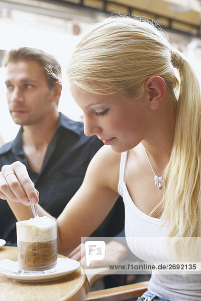 Close-up of a young woman and a young man seated at a table