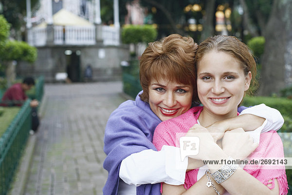 Portrait of a mature woman hugging her daughter from behind