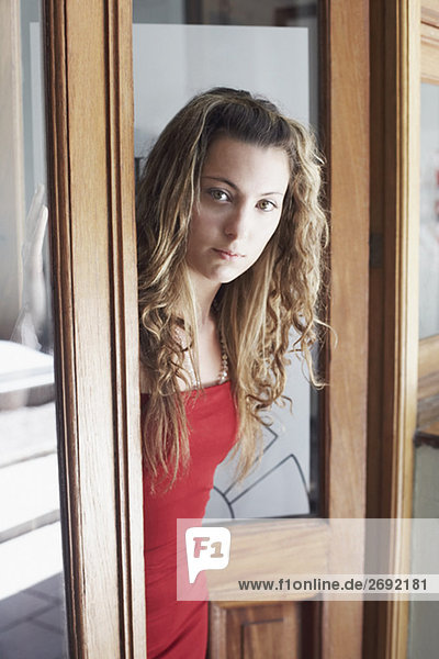 Portrait of a young woman standing at a door
