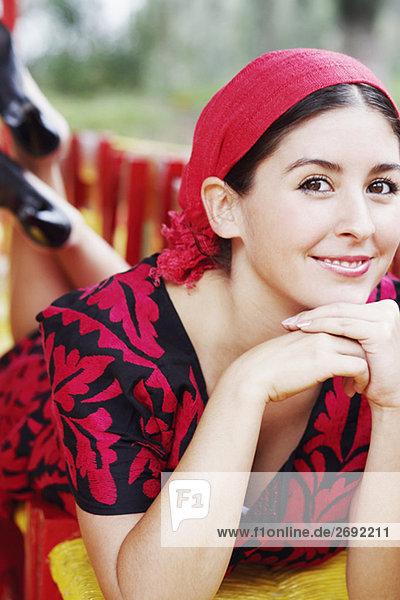 Portrait einer jungen Frau lächelnd mit der Hand auf dem Kinn
