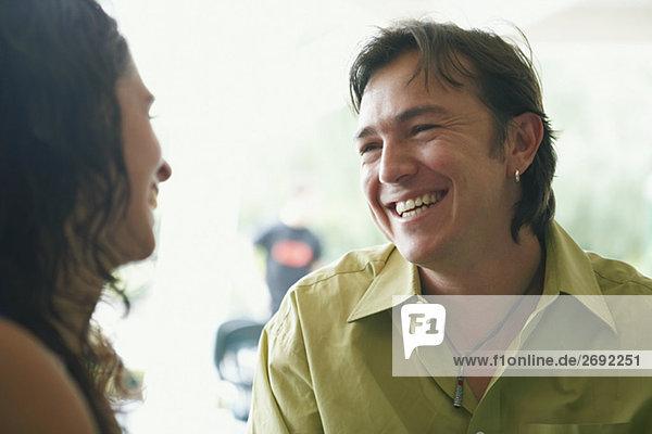 Nahaufnahme einer jungen Frau und ein Mitte Erwachsenen Mann Blick auf einander und lächelnd in einem restaurant