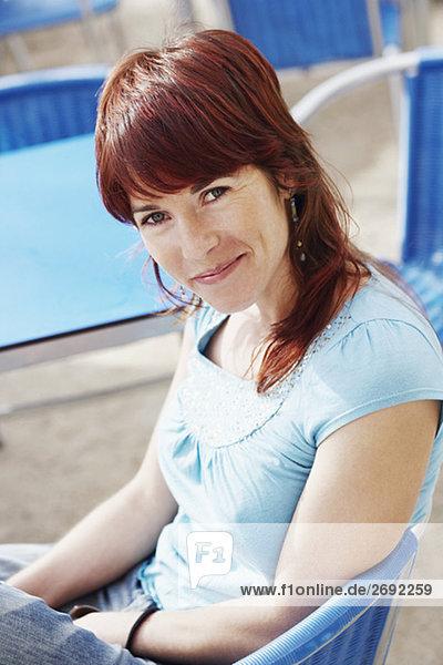 Portrait einer jungen Frau sitzen in einem Bürgersteig Café