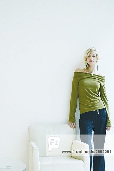 Portrait einer jungen Frau an einer Mauer gelehnt