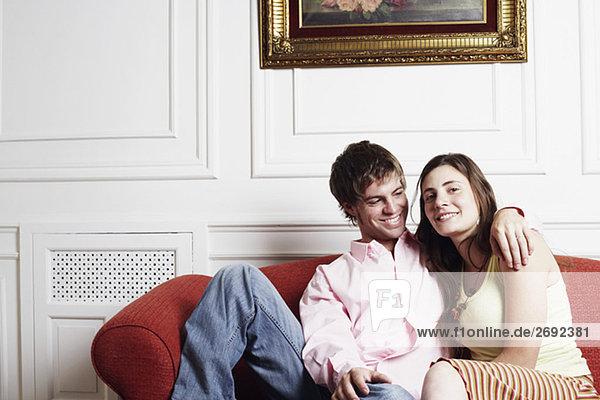 Porträt eines jungen Paares sitzen auf der couch