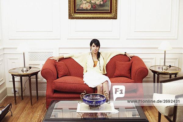 Portrait einer jungen Frau sitzt auf einer couch