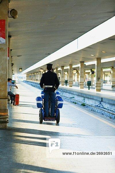 Rückansicht des zwei Polizisten Reisen Roller auf eine Zugbahnsteig  Rom  Italien